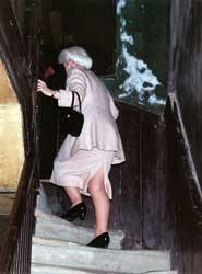 Lady Grade climbs the shadowy stairs to the attics